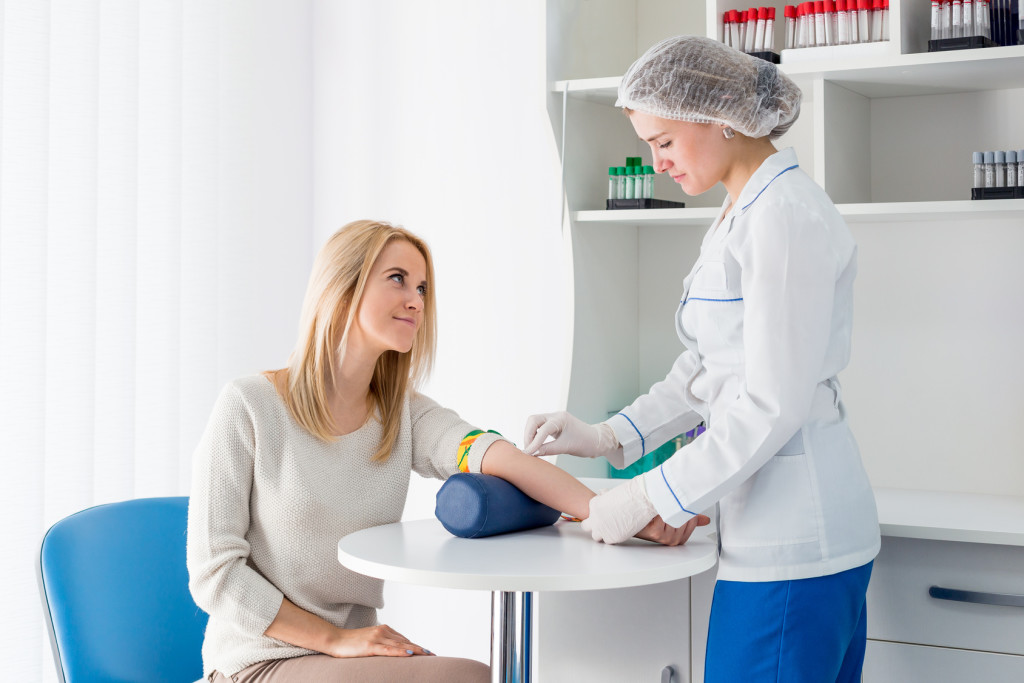 Preparation for blood test with beautiful young blond woman by female doctor in white coat medical uniform on the table in white bright room. Nurse rubbing a hand styryl patient tissue.